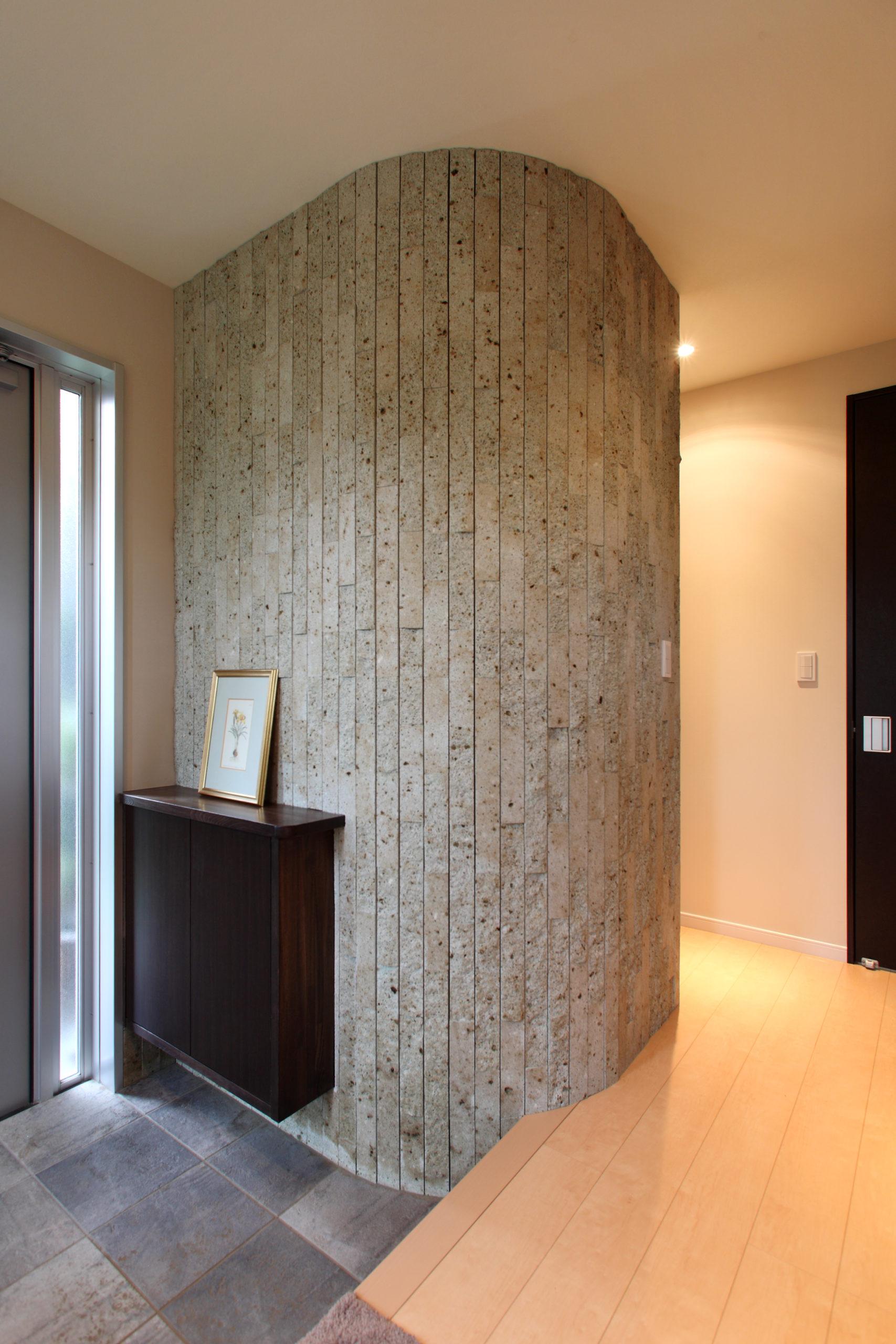 玄関には細い材料を用い、その画面に合わせた仕上げにしました 表面は少しゴツゴツさせ自然の感じを出しています