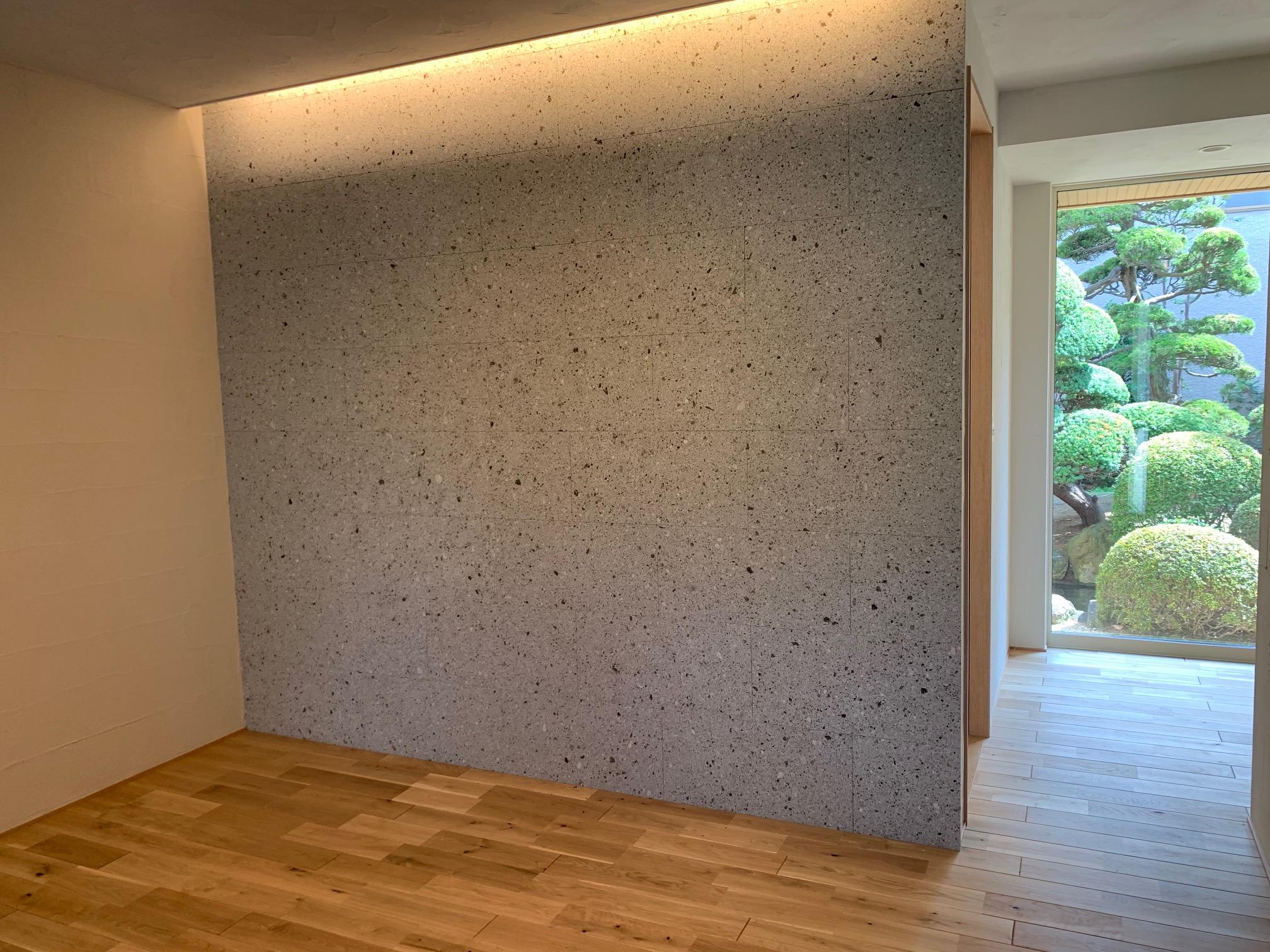 細目にダイヤ挽きで20×300×600を施工しました。1階ホールで玄関入って正面に貼ってあり存在感があります。ダウンライトの光で大谷石は温かく、柔らかな風合いを感じられます。